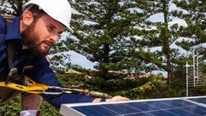 Ein Solarteur installiert eine Photovoltaikanlage.